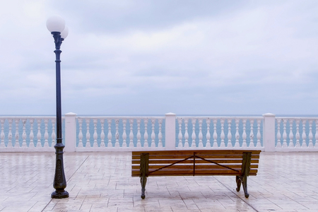 Bench and streetlight on beautiful terrace with sea view on waterfront. Stock Photo