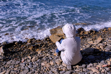 Woman in a white down jacket and hood sits on the shore and looks at the stormy sea waves beating against the stone shore. Back view.