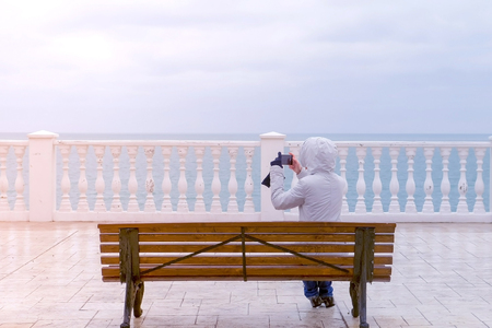 Woman in white jacket and hood shoots sea waves video on smartphone sitting on the bench on beautiful terrace with sea view on waterfront. Back view.