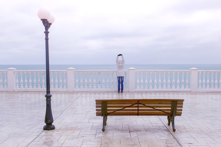 Woman in white jacket and hood on beautiful terrace with sea view on waterfront. Back view.