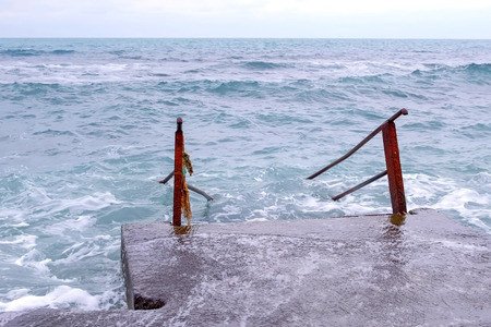 Stairs going into rough sea. Bad day at the beach with big waves.