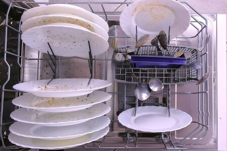 White dirty plates and spoon in dishwasher basket. Top view, close-up hand.