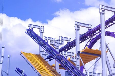 Construction of the attraction roller coaster at an amusement Park on blue sky background at Sunny day.