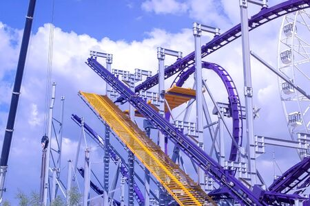 Install the roller coaster ride in the amusement Park on the blue sky background at Sunny day. Stok Fotoğraf