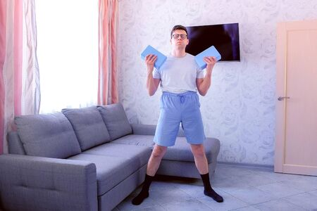 Funny nerd man in glasses and shorts is doing exercises for hand biceps with yoga blocks instead of dumbbells at home. Sport humor concept.