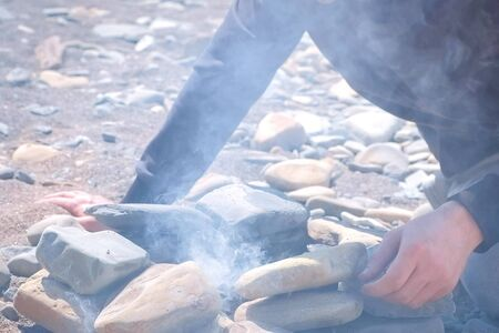 Dad and son are igniting the coals in the bonfire on the stones brazier with wooden sticks, hands closeup.