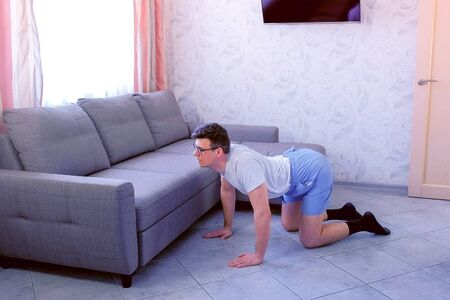 Funny nerd man in glasses and shorts is doing stretching exercise for back standing on all fours at home. Sport humor concept. Archivio Fotografico