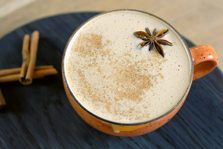 Cup of coffee capuccino with Badian on a tray. Close-up side view