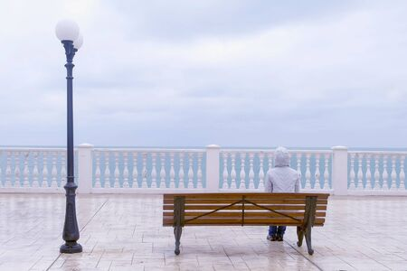 Woman in white jacket and hood is sitting on the bench on beautiful terrace with sea view on waterfront. Back view