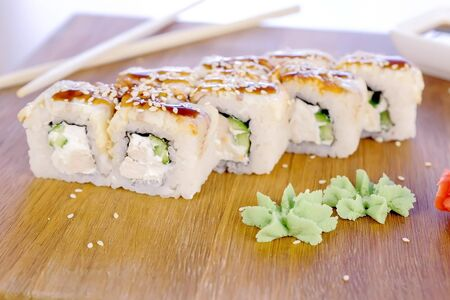Rolls with fish and sesame seed on top served in wooden board with wasabi, ginger and soy sause
