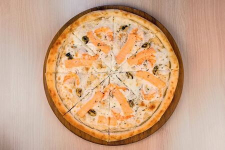 Slicing pizza with seafood and cheese on wooden board, close-up view
