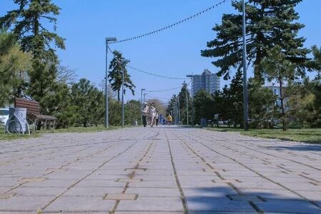 Anapa, Russia, 26-04-2019: People walk down the street revolution Avenue. Low angle view of the street with trees and plants on the squares. Resort town off-season. Editorial video.