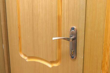 Wooden door with metal handle and lock indoors, closeup view. Reklamní fotografie