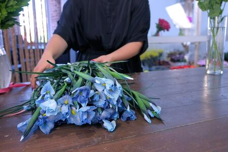 Floral business concept. Woman florist prapares iris flowers for bouquet tears leaves in floristic shop on wood table, hands closeup. Working in floristic studio store. Creating professional bunch.