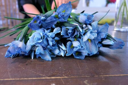 Creating professional bunch. Florist woman making bouquet from blue iris flowers on table for sale in shop, hands closeup. Working in floristic studio store. Floral business concept. Фото со стока