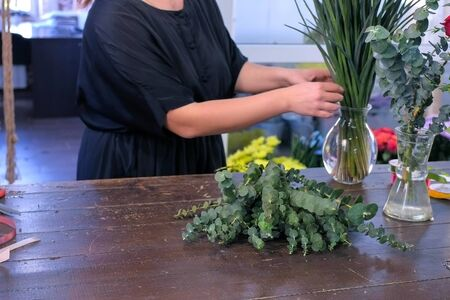 Floral business concept. Woman florist prepares eucalyptus and iris flowers for bouquet in shop for sale. She takes flowers fron vase and puts on table. Working in floristic studio store. Фото со стока