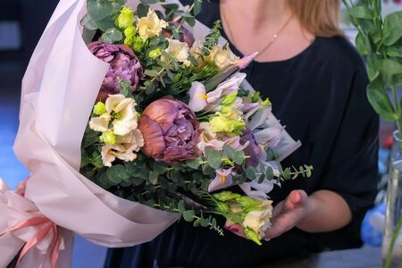 Floral business concept. Woman florist shows big lovely frower bouquet of eucalyptus branches, beige eustoma, brown maroon peony, blue iris in white paper in shop, hands closeup. Creating bunch. Фото со стока
