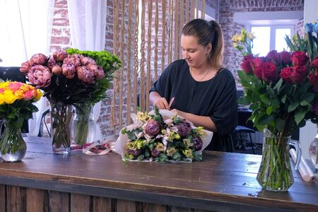 Floral business concept. Florist woman makes big flower bouquet of eucalyptus branches, beige eustoma, brown maroon peony, blue iris and ties stems of ribbon in flower shop. Create professional bunch.