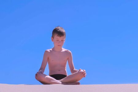 Boy in swimming trunks is relaxing on vacations. Child boy is meditating sitting in lotus pose with closed eyes on sandy beach on blue sky background. Yoga breath practice. Travel tourism in summer. Reklamní fotografie
