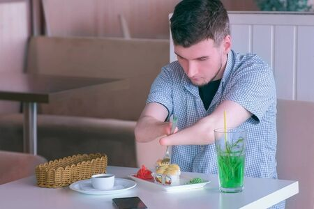 Problem of adaptation to usual life guy without wrists. Disabled man with two amputated stump hands eats sushi rolls in cafe with fork. Independent Invalid person with disabilities. Banco de Imagens