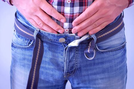 Man with buckled jeans and belt. He is stroking and touching his stomach after heavy dinner. Waist closeup.