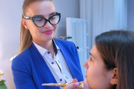 Makeup artist woman doing make up for young girl putting concealer. Process making makeup. Glamour professional visagiste working with brush on model face applying tone to skin in beauty salon studio.