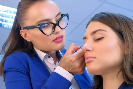 Makeup artist glue artificial eyelashes to girl in beauty salon. Professional visagiste making extension lashes. Glamour stylish fashion industry. Beauty business working concept. Young woman stylist. Stockfoto