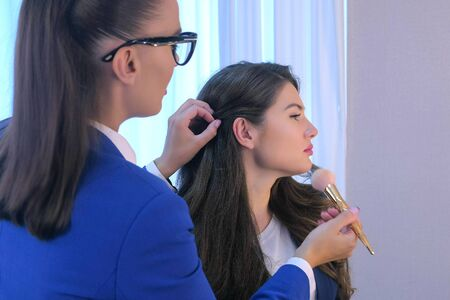 Hair stylist is working with young woman making hairstyle and makeup in beauty salon. Glamour fashion industry. Beauty business concept. Girl in beauty salon. Visagiste doing make up and hairdo. Stockfoto