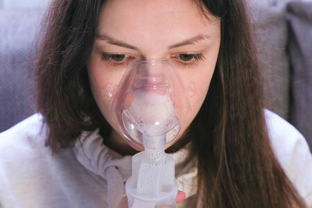Use nebulizer and inhaler for the treatment. Young woman inhaling through inhaler mask, close-up front view