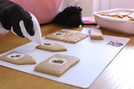 Womans decorate with sugar sweet cookies for gingerbread houses