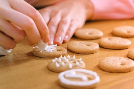Womans hands decorate christmas cookies with sugar sweet icing