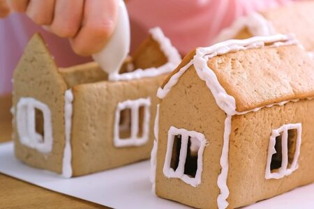 Womans hands make gingerbread houses glues details with sugar sweet icing. Cooking homemade gingerbread house