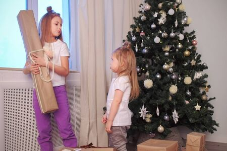 Two sisters take away each others gift box near Christmas tree at home. Younger sister is offended by older. New Year interior in winter xmas holidays at home. Girls put gifts under the tree. Standard-Bild