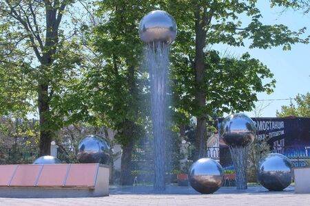 Anapa, Russia, 26-04-2019: Water fountain with metal balls on the waterfront of the city. Spring warm day off-season in resort town. Editorial video.