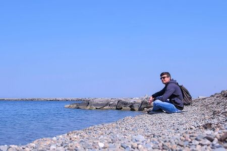 Happy traveller is sitting on sea stone beach admire seascape at sunny spring day. Guy in modern style wear with backpack in sunglasses alone on vacation. Travel journey tourist on beach. Stok Fotoğraf