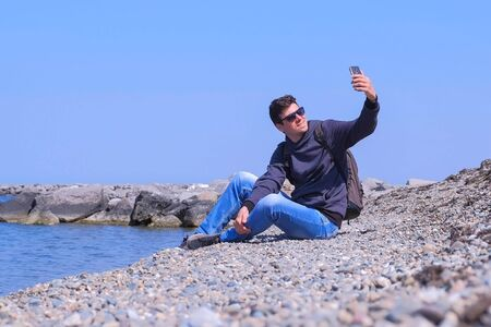 Young man traveller is sitting on sea stone beach and making selfie on mobile phone. Guy tourist on his spring vacations. He is with backpack wearing jeans and sweatshirt in sunglasses. Travel journey