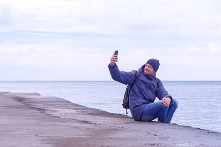 Tourist in warm clother hat and jacket takes a pictures on mobile phone on sea background. Man traveller makes selfie on smartphone aits on waterfront at sea in winter. Overcast rainy day at seaside.
