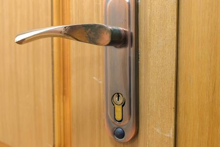 Maniglia in metallo e serratura su porta di legno, primo piano. Porta interna in ufficio.
