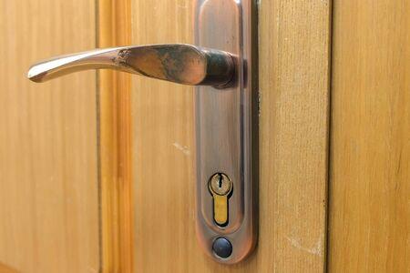 Metalowy uchwyt i zamek na drewnianych drzwiach, widok zbliżenie. Drzwi wewnętrzne w biurze.