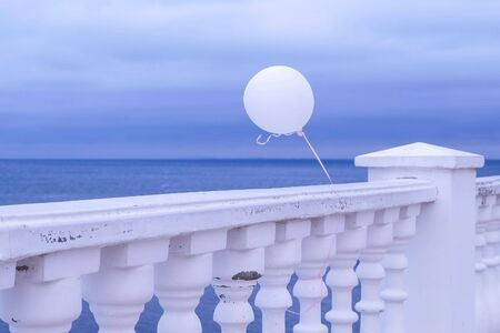 Promenade overlooking the sea through the fence on a gloomy rainy day. White balloon in the wind tied to the fence. Beautiful seascape.