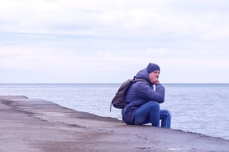 Tourist at sea off-season. He is wearing on hat, jacket, jeans with backpack. Man traveller sits on old waterfront at sea in winter day and looks at seascape. Stock fotó