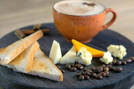 Cheese coffee with melted cheese, pieces of cheese and bread toasts on a tray, side view.