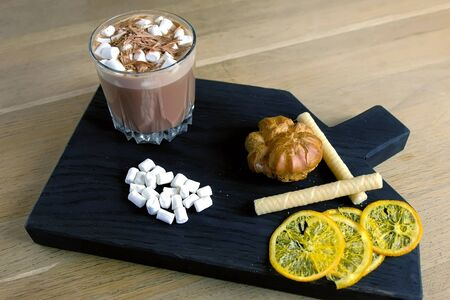 Cocoa with marshmallow in rock glass on a wood black tray with cake and lemon. Close-up view Imagens