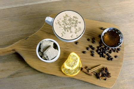 Cup of coffee with halva served on a tray with honey and coffee beans