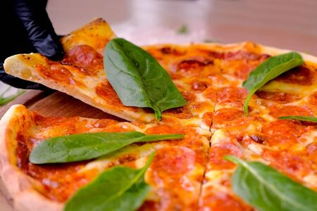 Cook takes a slice of salami pizza with spinach leaves, hands in rubber gloves close-up side view Imagens