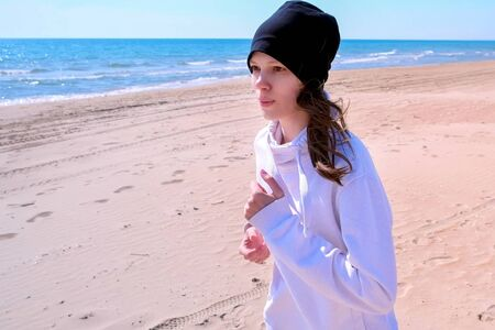 Portait of young woman is jogging on sea sand beach at morning. Girl beginner jogger is running on seaside. Sport and fit outdoors. She is wearing hoodie and hat.