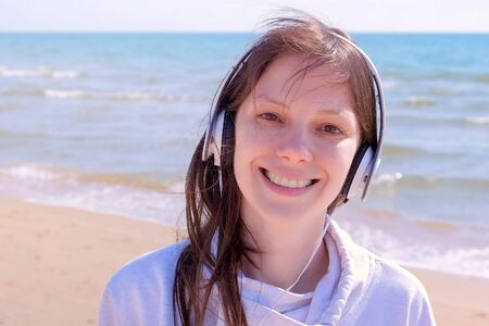 Portrait of happy young girl is shaking her head in headphones and listening music. Brunette woman is walking on sea sand beach enjoying her time. Imagens