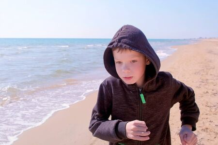 Portrait of child boy is running at sea sand beach. He is in hoodie and hood. Little jogger in windy sunny day at seashore. Imagens