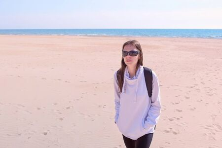 Young woman traveller in sportswear and sunglasses with backpack. She is walking at sea sand beach. Brunette girl on vacation at ocean in sunny day. Outdoor activities at sea.