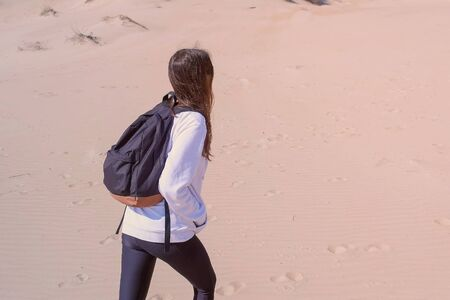 Woman traveller with backpack in sportswear is walking on sand dunes on seashore. Outdoor activities on vacation. Girl tourist in hiking, back view.